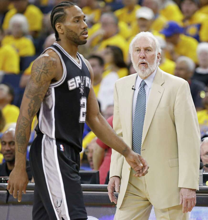 Spurs' Kawhi Leonard walks to the bench past head coach Gregg Popovich during second half action of Game 1 in the Western Conference fFinals against the Golden State Warriors on May 14, 2017 at Oracle Arena in Oakland, Calif. Photo: Edward A. Ornelas /San Antonio Express-News / © 2017 San Antonio Express-News