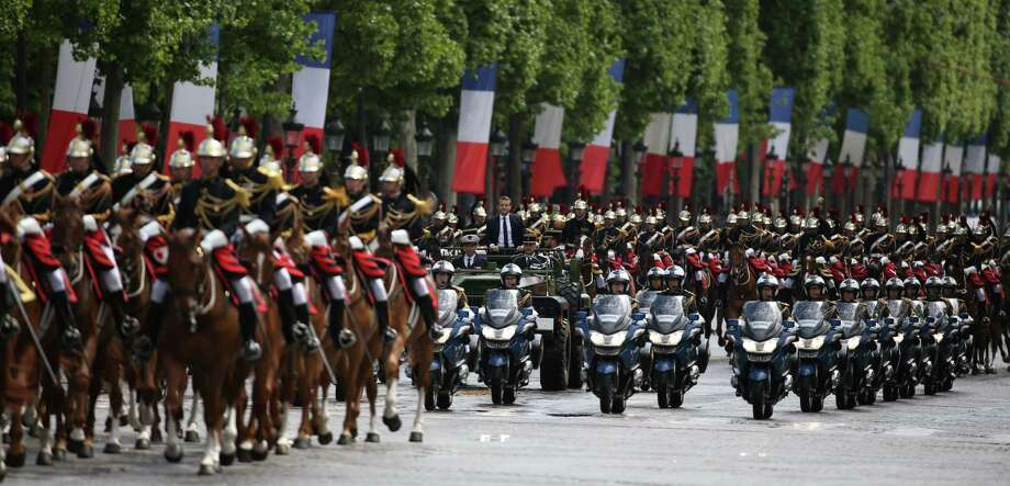 TOPSHOT - French President Emmanuel Macron (C) parades in a car on the Champs Elysees avenue after his formal inauguration ceremony as French President on May 14, 2017 in Paris. / AFP PHOTO / CHARLY TRIBALLEAUCHARLY TRIBALLEAU/AFP/Getty Images Photo: CHARLY TRIBALLEAU / AFP or Licensors