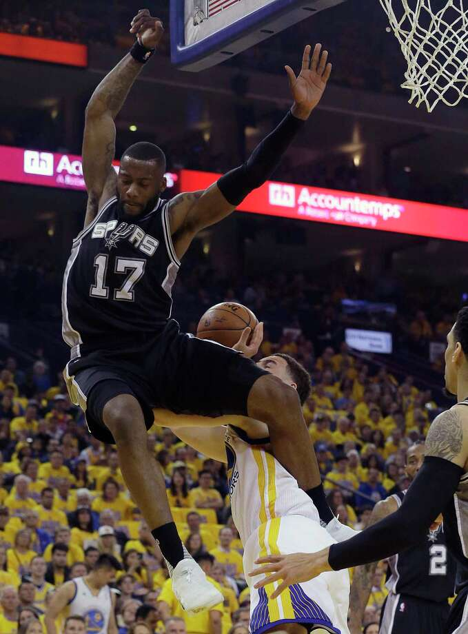 Golden State Warriors guard Klay Thompson, bottom center, is fouled by San Antonio Spurs guard Jonathon Simmons (17) during the first half of Game 1 of the NBA basketball Western Conference finals in Oakland, Calif., Sunday, May 14, 2017. (AP Photo/Jeff Chiu) ORG XMIT: OAS106 Photo: Jeff Chiu / Copyright 2017 The Associated Press. All rights reserved.