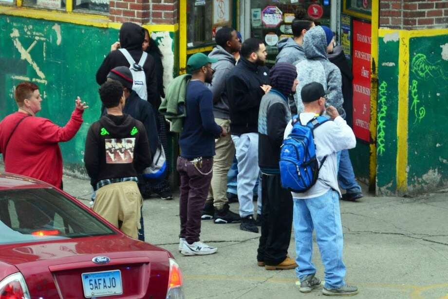 People gather to watch after Jayson Negron was shot by police on Tuesday. Photo: Christian Abraham / Hearst Connecticut Media / Connecticut Post