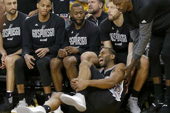 San Antonio Spurs' Kawhi Leonard reacts after being injured on a play as teammates Manu Ginobili (from left), Dejounte Murray, Jonathon Simmons, David Lee, and Dewayne Dedmon look on during second half action of Game 1 in the Western Conference Finals against the Golden State Warriors held Sunday May 14, 2017 at Oracle Arena in Oakland, CA. The Warriors won 113-111.