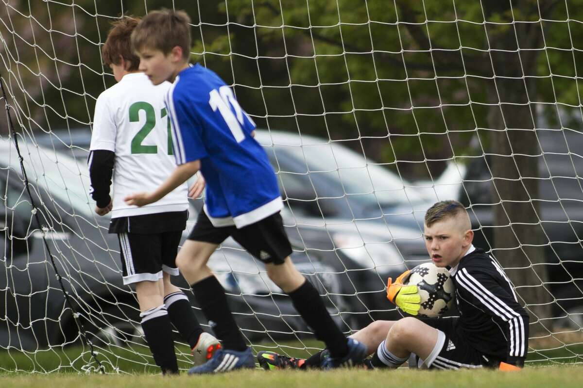 Midland Fusion's Samuel Rovoll makes the save against Michigan Rush Lansing North during the Annual Midland Invitational Tournament at the Midland Soccer Complex on Sunday.