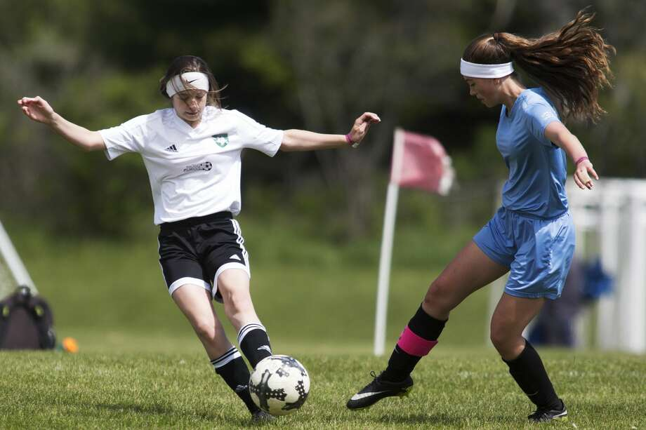 Midland Fusion's Brianna St.Dennis controls the ball while being defended by SCS United's Sophia LaPinta during the Annual Midland Invitational Tournament at the Midland Soccer Complex on Sunday. Photo: Theophil Syslo