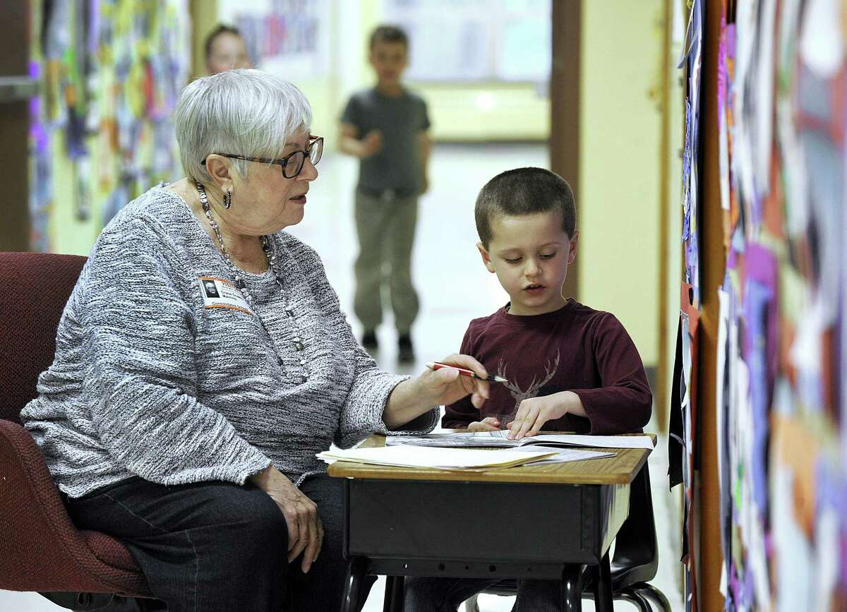 Grace Scalera Manning reads with kindergartner Emilio Soto, 5, in the hallway at Consolidated School on Wednesday.