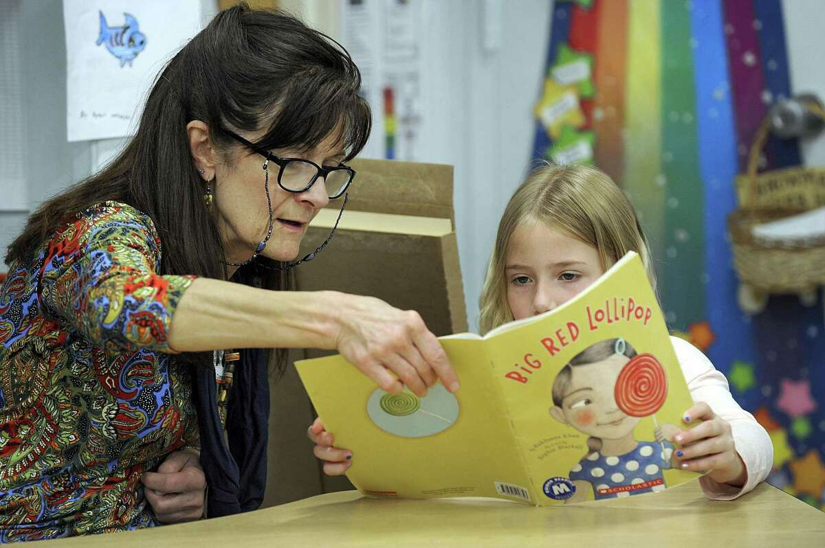 Kathy Hull reads with Kayla Baum, 7, a second-grader at Consolidated School on Wednesday. The New Fairfield school has partnered with the town's Senior Center for its Senior Buddies Program, which lets seniors volunteer with kids each week.