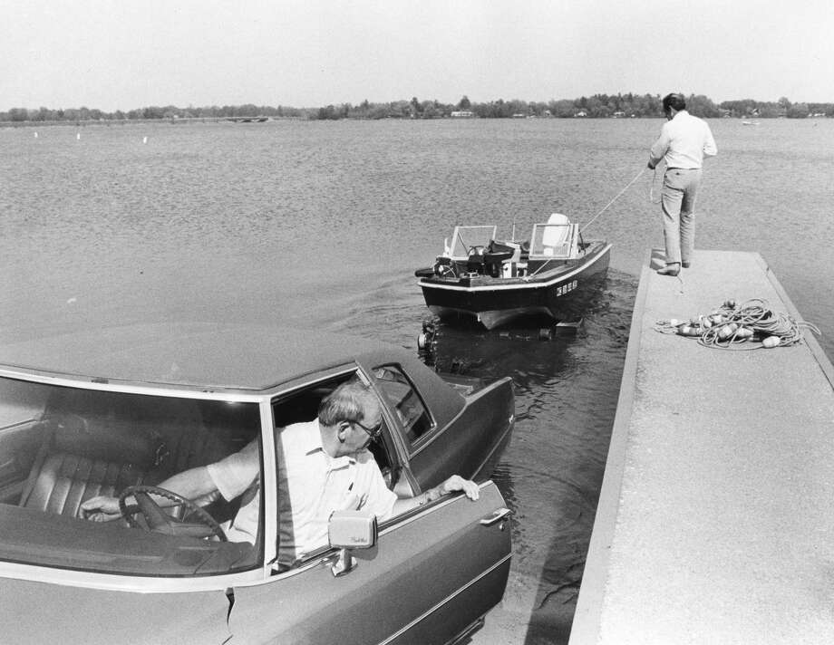 Tom Sian (in car) of Sanford and Jim St. Louis, right, of Davenport, Iowa, launch a boat. May 1985 Photo: Daily News File
