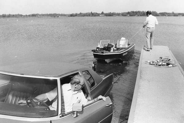 Tom Sian (in car) of Sanford and Jim St. Louis, right, of Davenport, Iowa, launch a boat. May 1985