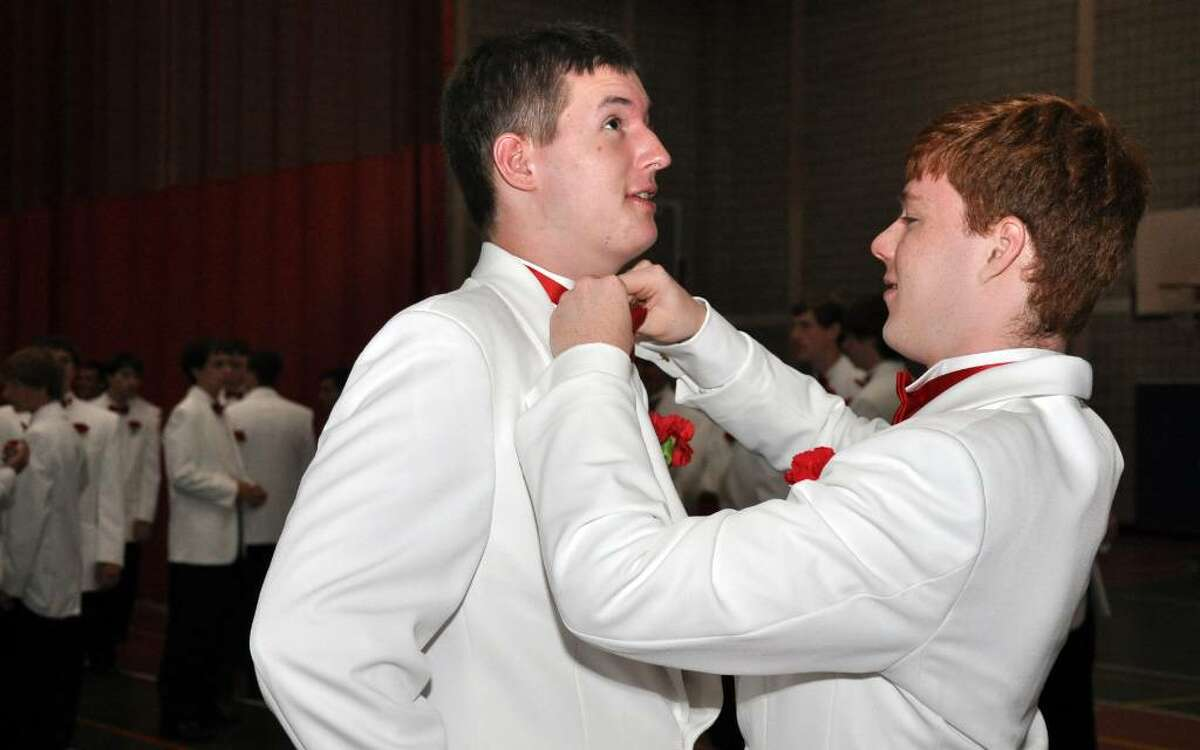 Dan O'Rourke, of Newtown helps classmate Quinn Rooney, of Stratford, with his bow tie in the staging area before the start of Fairfield College Preparatory School's 68th Commencement ceremony on Sunday, June 6, 2010.