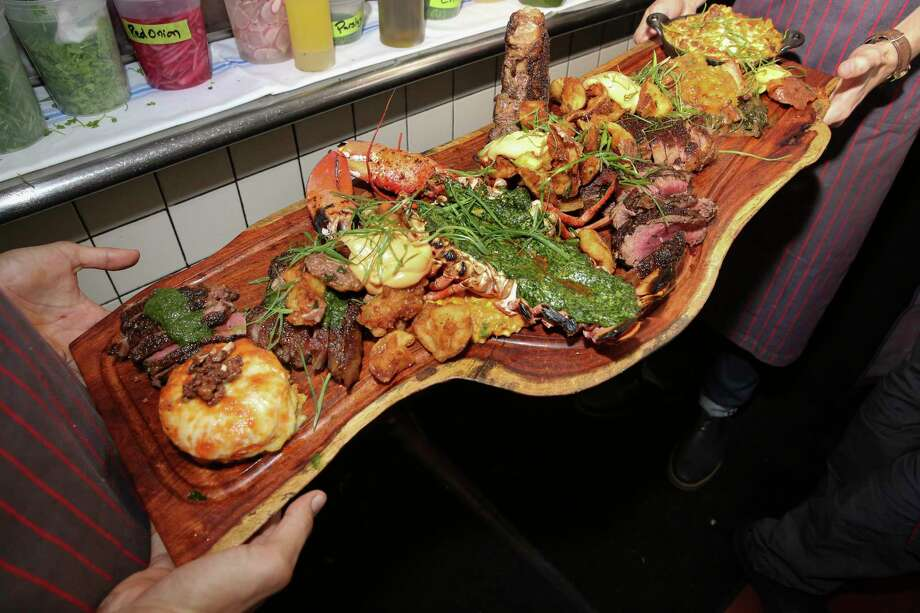 A five-person Baller Board at One Fifth Steak containing Wagyu strip with chimichurri, crispy potatoes with roasted garlic aioli, hearth-roasted lobster Rockefeller, porterhouse, dry-aged tomahawk, maque choux, sweet potato gratin, braised greens, pork belly and grilled peaches and Lamburger Helper. Photo: Yi-Chin Lee, Houston Chronicle / © 2017  Houston Chronicle