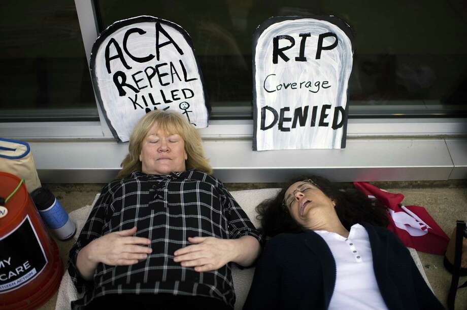 Maureen Quinn, left, and Maria Palmer pretend to be dead as protestors gather before a town hall held by New Jersey Republican Rep. Tom MacArthur in Willingboro, N.J. on Wednesday. MacArthur is a Republican who played a key role in helping the GOP-led U.S. House pass an Affordable Care Act replacement bill. Photo: Joe Lamberti /Associated Press / Camden Courier-Post