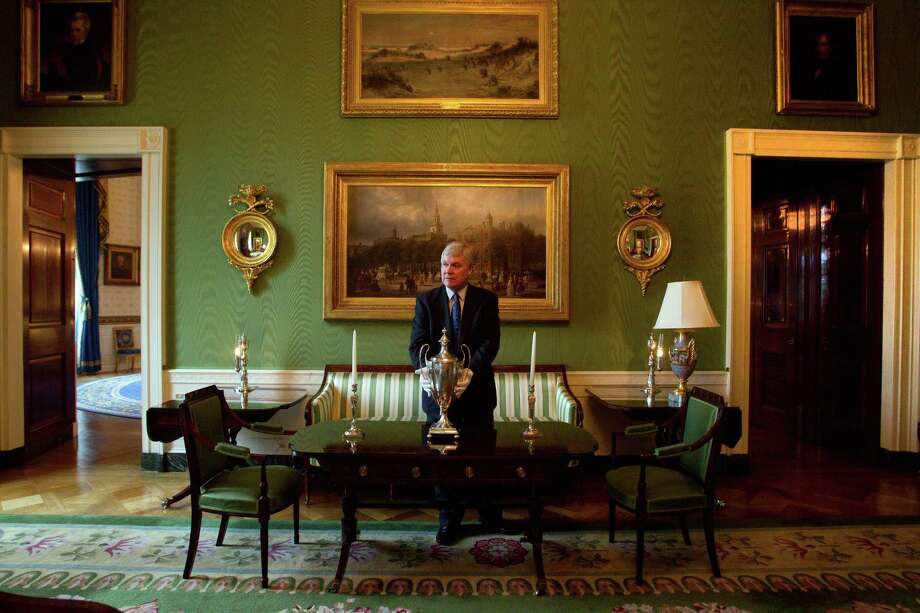 "William Allman, chief White House curator, in the Green Room of the White House, in Washington, March 9, 2011. Allman works hard to keep a low profile as he tends to the art and antiques around the White House. Behind Allman are two paintings, ""Sand Dunes at Sunset, Atlantic City,"" by Henry Ossawa Tanner, at top center, and ""Independence Hall in Philadelphia,"" by Ferdinand Richardt.  (Doug Mills/The New York Times) Photo: DOUG MILLS, STF / NYTNS"