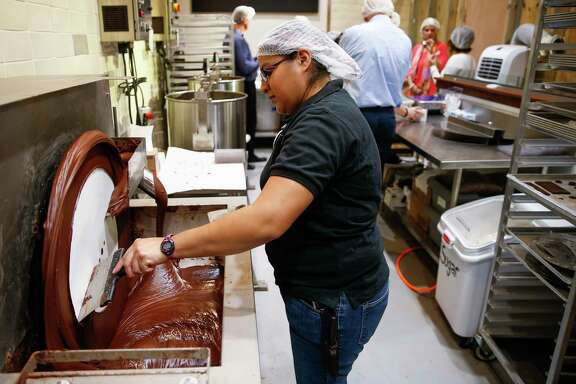 Central Market lead chocolatier Margarita Elizondo tempers chocolate at the Bean to Bar area, where employees turn cacao beans to chocolate.