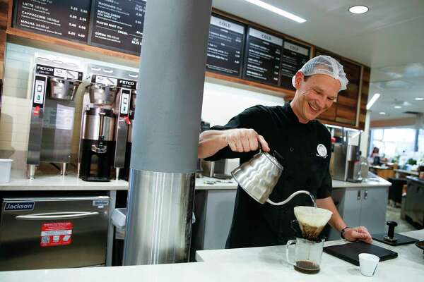 Central Market barista Shawn Arzykowski makes coffee at the new coffee bar, which is part of the store.s $10 million renovation.