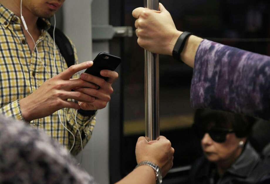 Jeff Korcal listens to a podcast and attempts to send texts as his phone service comes in and out while riding on the Muni L train Sept. 14, 2016 in San Francisco, Calif. Photo: San Francisco Chronicle File Photo / Leah Millis/ The Chronicle