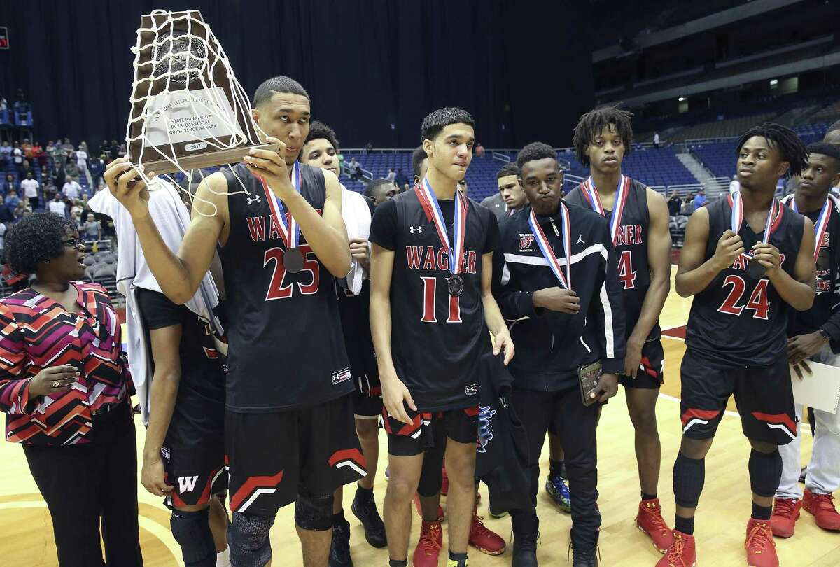 Tristan Clark holds his teams second place trophy as Wagner loses to the Cypress Falls Eagles in the state championship basketball game for class 6A boys at the Alamodome on March 11, 2017.