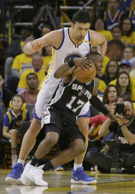 San Antonio Spurs guard Jonathon Simmons (17) is fouled by Golden State Warriors center Zaza Pachulia, top, during the first half of Game 1 of the NBA basketball Western Conference finals in Oakland, Calif., Sunday, May 14, 2017. (AP Photo/Jeff Chiu)