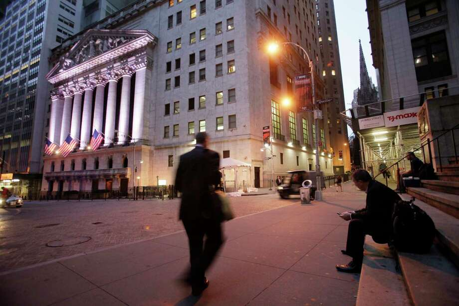 """FILE - In this Oct. 8, 2014, file photo, a man walks to work on Wall Street, near the New York Stock Exchange, in New York. Shares edged higher Monday, May 15, 2017, in Europe and Asia, despite worries of disruptions from the """"WannaCry"""" ransomware cyberattack over the weekend. (AP Photo/Mark Lennihan, File) ORG XMIT: NYBZ100 Photo: Mark Lennihan / Copyright 2016 The Associated Press. All rights reserved. This m"""