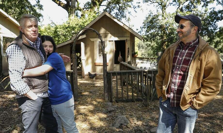 Sasha Motola-Walden hugs her father, Mark Walden, as her father, Glenn Motola, looks on. Photo: Russell Yip, The Chronicle