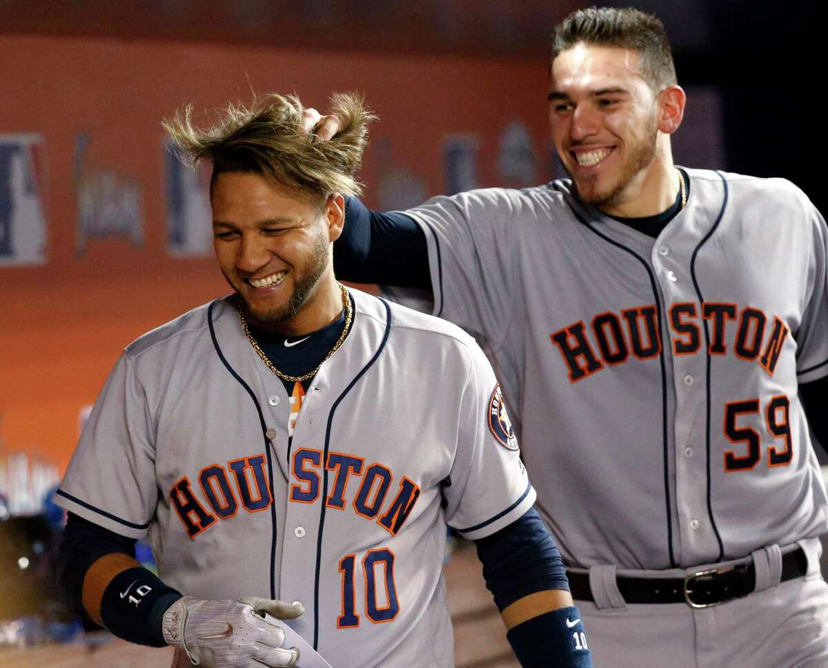 Houston Astros starting pitcher Joe Musgrove (59) messes up the hair of Yuli Gurriel (10) after Gurriel hit a grand slam during the sixth inning of a baseball game against the Miami Marlins, Monday, May 15, 2017, in Miami. Gurriel drove in Evan Gattis, Carlos Correa, and Josh Reddick. (AP Photo/Wilfredo Lee)