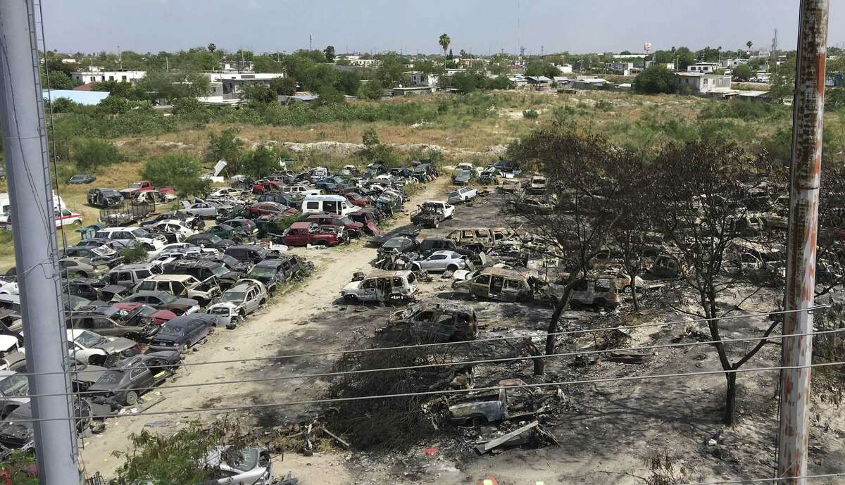 Vehicles, many burned and destroyed in ongoing battles between drug cartels fighting for dominance in Reynosa, Mexico, sit in a lot. Clashes there since late April have left 28 people dead.