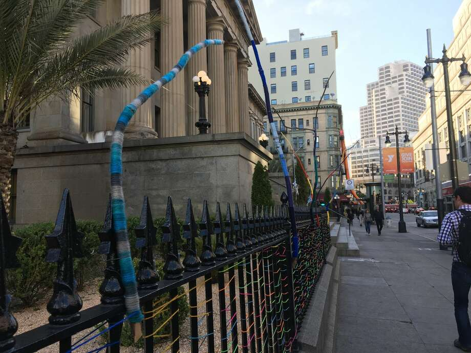 An art project by artist Cristina Velázquez is seen at the Old Mint in San Francisco, featuring yarn woven around branches and the building's fence. Photo: Dianne De Guzman / SFGATE