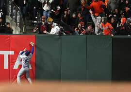 San Francisco Giants' Buster Posey's solo home run in 7th inning lands out of reach of Los Angeles Dodgers' Cody Bellinger during MLB game at AT&T Park in San Francisco, Calif., on Monday, May 15, 2017.