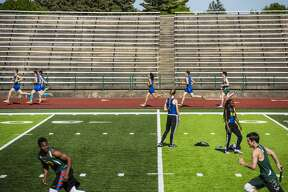 Athletes compete in the 1600 meter run as others warm up on the field at a track and field meet hosted at Mount Pleasant High School on Monday.