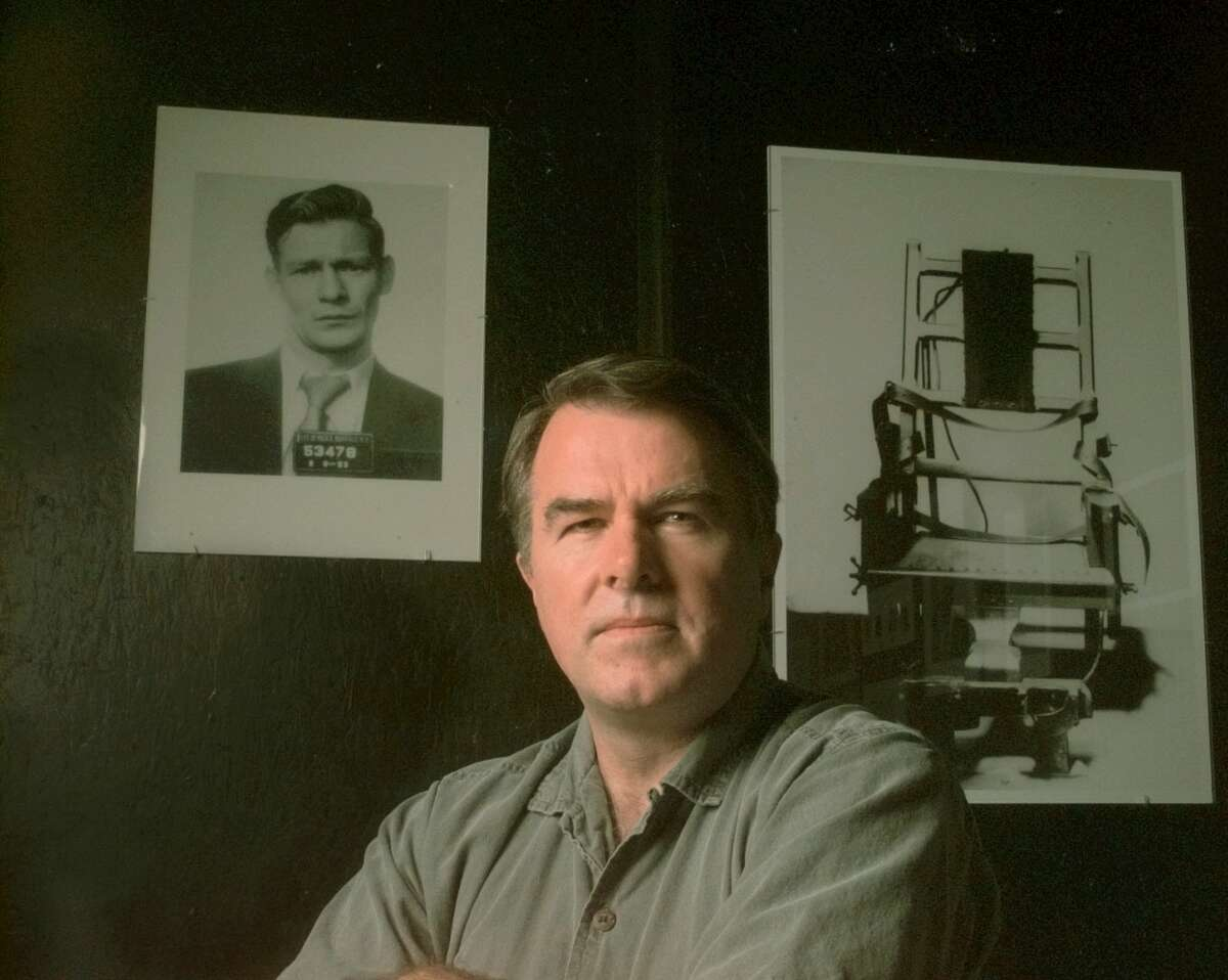 Writer Scott Christianson poses Tuesday, Sept. 19, 2000, in the Time and Space Limited gallery in Hudson, N.Y., with two photos from his documentary photo exhibit that accompanies his book 'Condemned: Inside the Sing Sing Death House'. At the left is Maurice O'Dell in a Buffalo Police headshot from Feb. 8, 1953. O'Dell was executed in Sing Sing on Jan. 7, 1954. The right photo is the Sing Sing electric chair circa 1940s. (Associated Press0