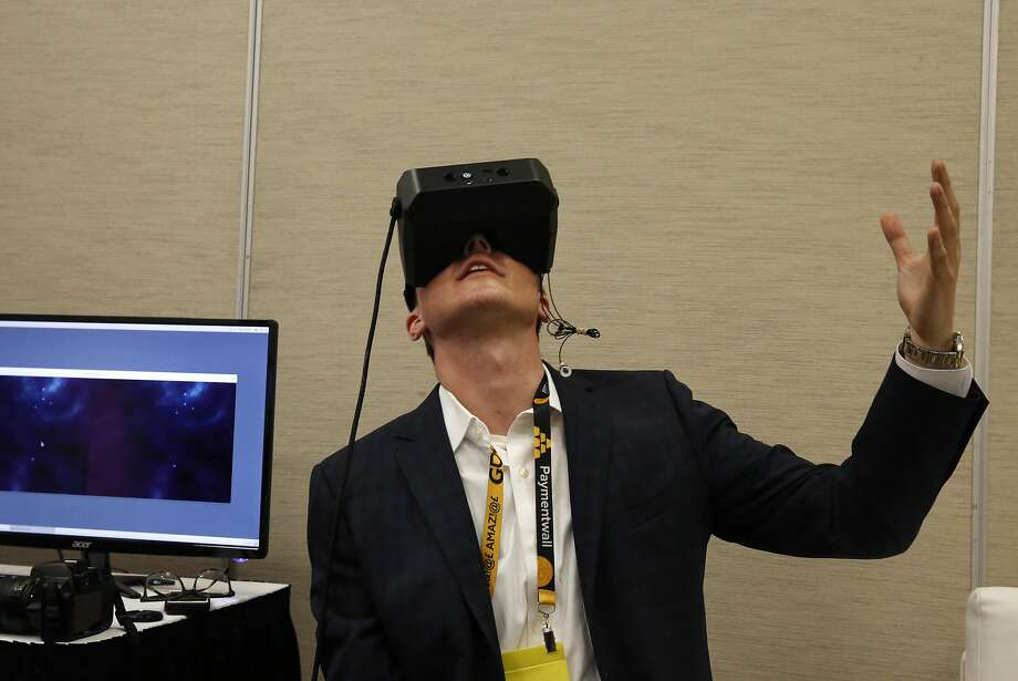 """Will Mason, a co-founder of UploadVR, tries out  MindLeap neuro-goggles during the Game Developers Conference at Moscone Center South on March 3, 2015, in San Francisco. The company has been sued by a former employee who claims the startup and its co-founders cultivated a hostile, """"boys club"""" work environment. Photo: Leah Millis, The Chronicle"""