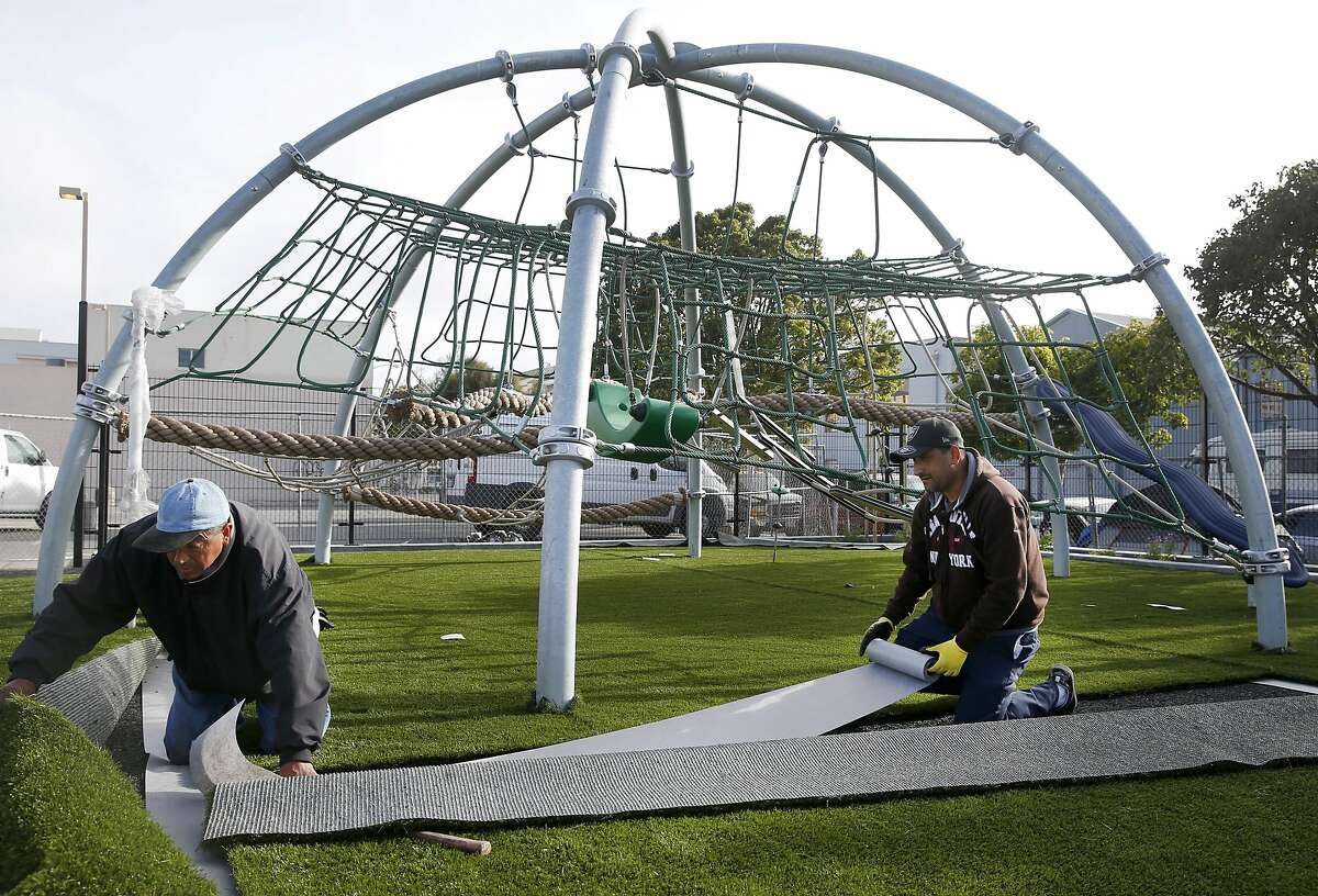 Workers install artificial turf in the playground of a park under construction at 17th and Folsom streets in San Francisco, Calif. on Tuesday, May 16, 2017. San Francisco is meeting its goal to have a park within a 10-minute walk from every home in the city.