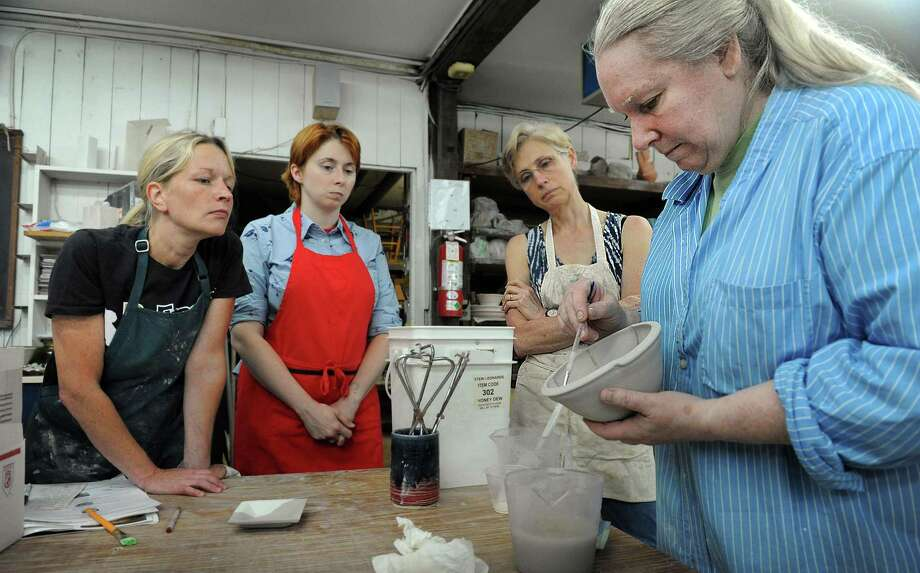 From left, Kristen Backus, Stepanie Fuda and Lisa Cioean, students in Clare Lewis's ceramics class at the Brookfield Craft Center, watch her glazing instruction, Wednesday, August 12, 2015. Photo: Carol Kaliff / Hearst Connecticut Media / The News-Times