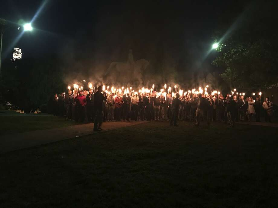 Protesters carry torches at a demonstration Saturday against the removal of a Confederate memorial in Charlottesville, Va. Photo: Allison Wrabel, Associated Press