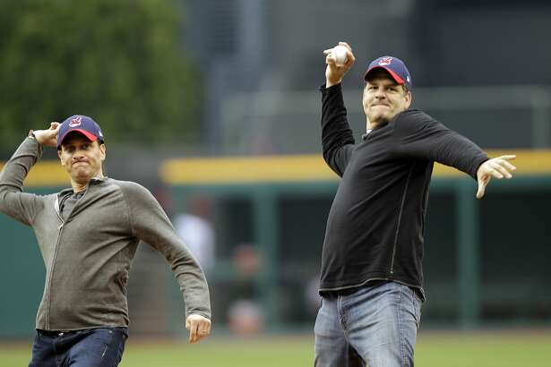 FILE - In this May 8, 2012, file photo, ESPN radio hosts Mike Greenberg, left, and Mike Golic throw out first pitches before a baseball game between the Cleveland Indians and the Chicago White Sox in Cleveland. The network announced Tuesday, May 16, 2017, that Greenberg would be leaving the longtime morning radio show he co-hosts with Golic to host a new morning TV show on ESPN TV that will premier Jan. 1. (AP Photo/Mark Duncan, File)