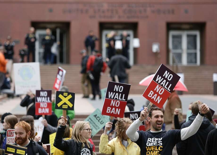 People protest outside as the Ninth U.S. Circuit Court of Appeals prepares to hear arguments on President Trump's revised travel ban in Seattle, Washington, on May 15, 2017. A second federal appeals court in Richmond, Va., has also taken up the ban. A / AFP PHOTO / Jason RedmondJASON REDMOND/AFP/Getty Images Photo: JASON REDMOND, AFP/Getty Images