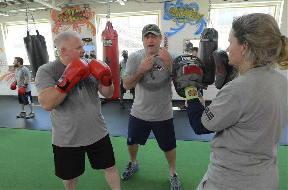 Scott Schweitzer, center, works with Chris Munger and Suzanne Parker during a class of the new Veterans Boxing Club at Revolution Training in Stamford on May 6, 2017. Schweitzer founded the club. Photo: Matthew Brown / Hearst Connecticut Media / Stamford Advocate