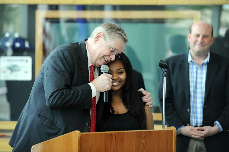 Stamford mayor David Martin hugs AITE student Keyara Zamor during a ceremony honoring Zamor's life-saving usage of CPR inside Government Center in Stamford, Conn. on Tuesday, May 16, 2017. Zamor saved her six-year old cousins life using CPR, which she learned during AITE's Hands for Life event in 2015. Photo: Michael Cummo / Hearst Connecticut Media / Stamford Advocate