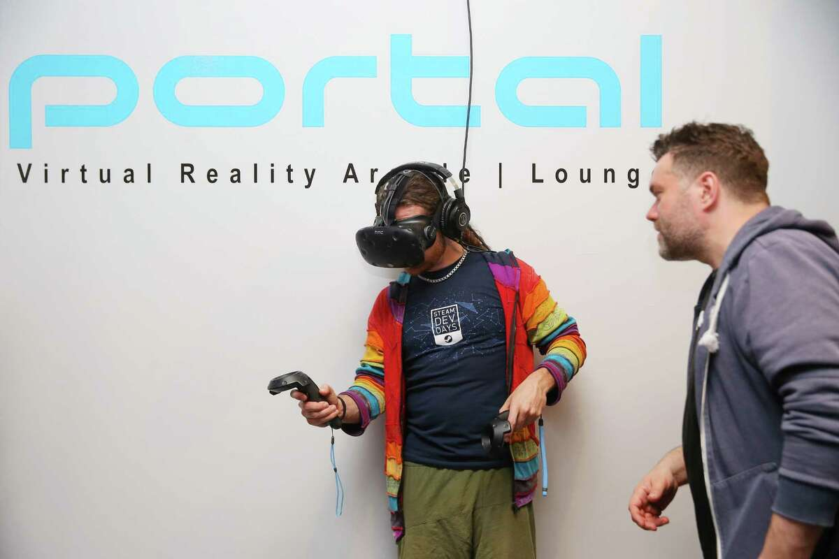Ryan Boudinot, right, assists Joshua Du Chene as he begins Richie's Plank Experience at Portal Virtual Reality Arcade and Lounge, May 8, 2017, during an industry night party.