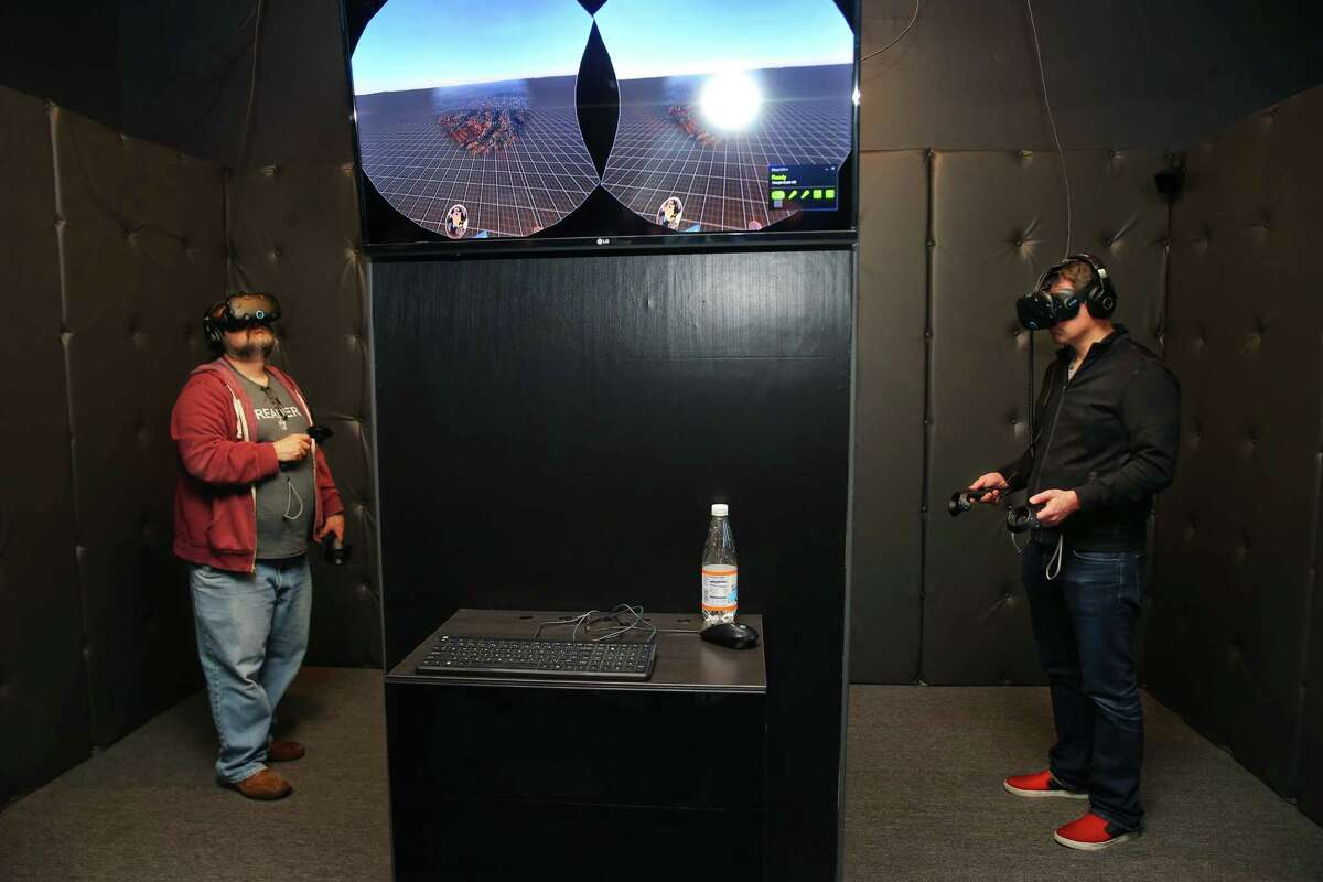 Andy Romine, left, and Rob Agee try out VR games at Portal Virtual Reality Arcade and Lounge, May 8, 2017, during an industry night party.
