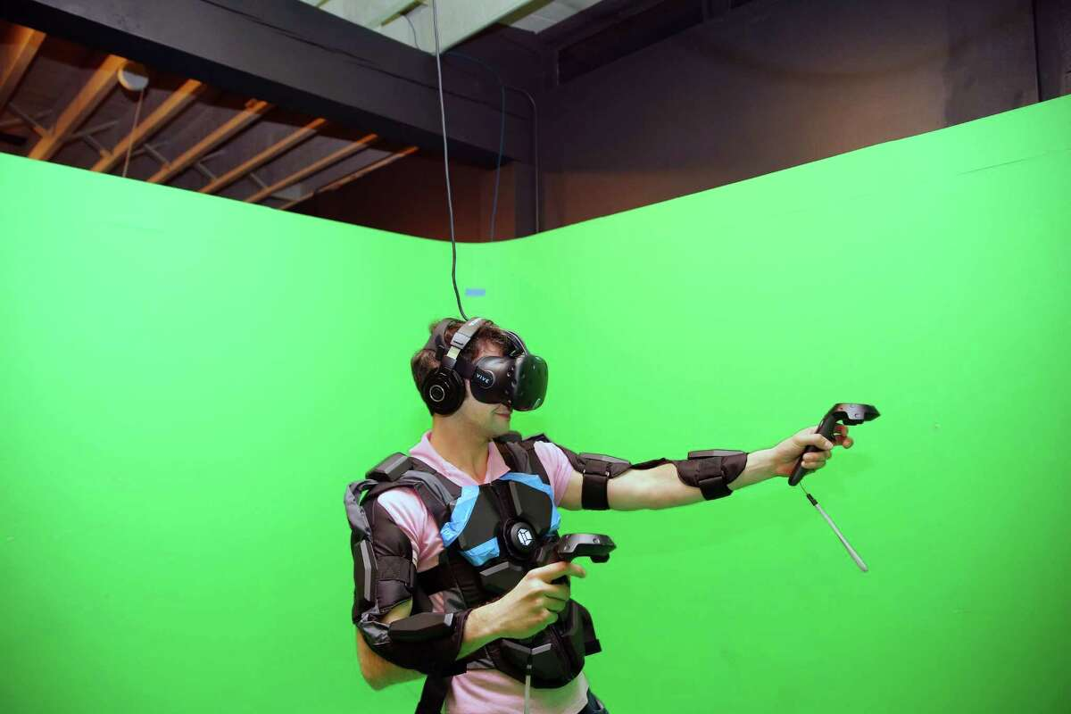 A man plays a virtual reality game at Portal Virtual Reality Arcade and Lounge, May 8, 2017, during an industry night party.