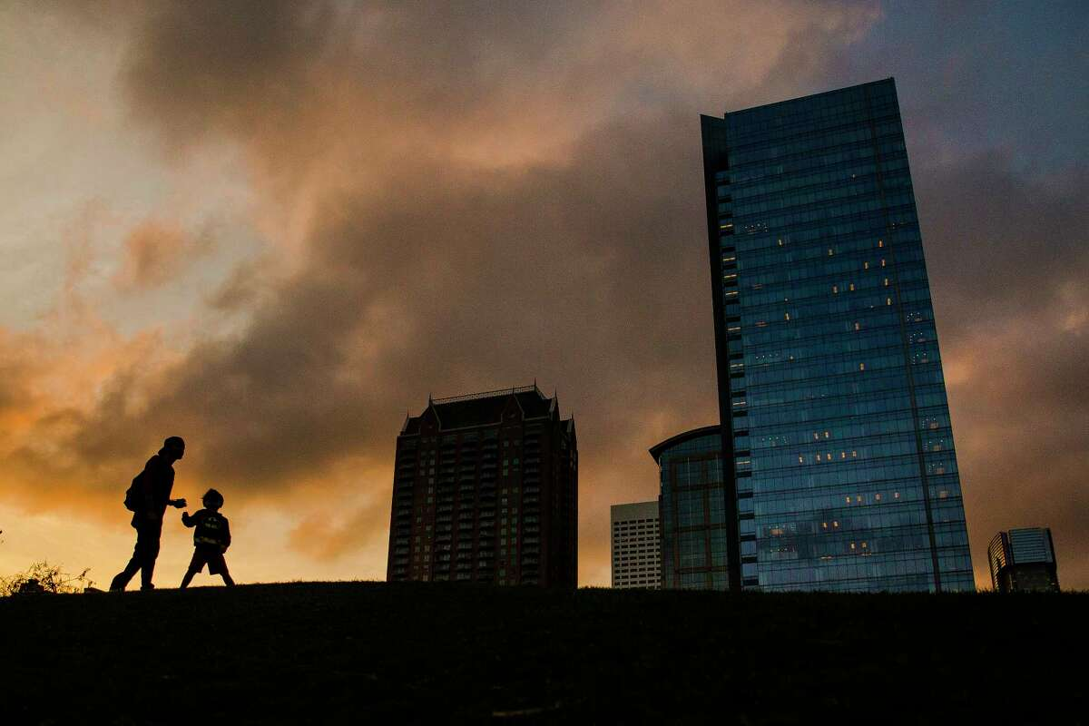 Angel Chavez and his 3-year-old son, Kaivon, play on a hill at Discovery Green as the sun sets.