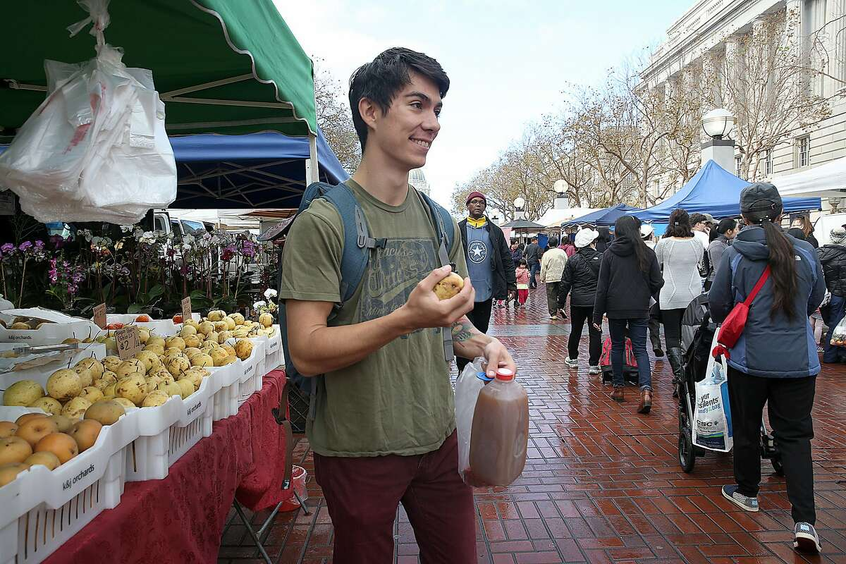Andrew Gonzales buys pear apples with his food stamp tokens at the Heart of the City Farmer's Market at the civic center on Wednesday, November 23, 2016, in San Francisco, Calif.