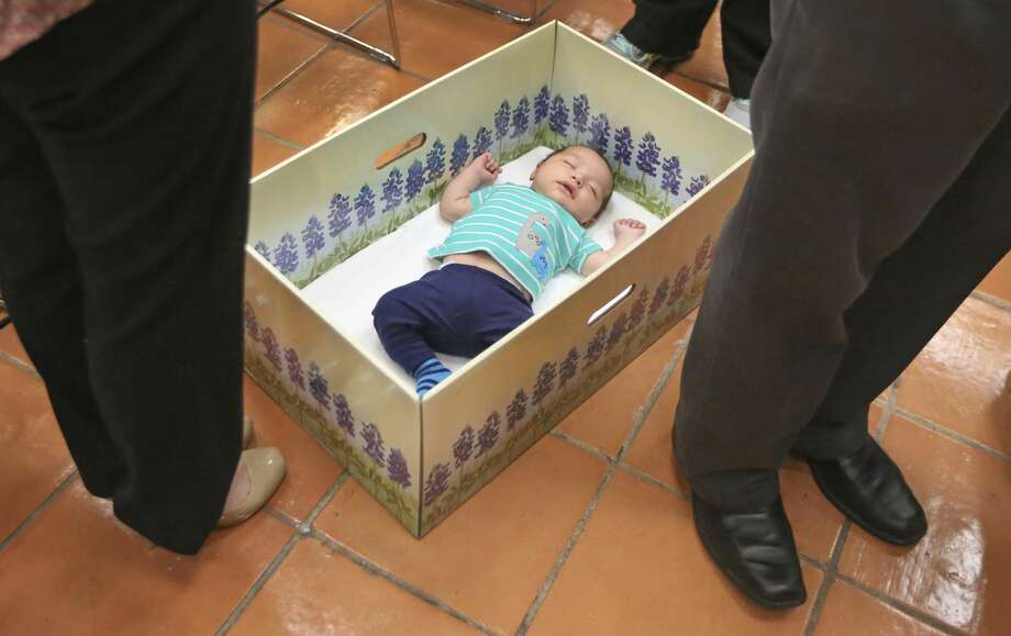 - In a May 3, 2017 photo,six-week-old Mason Salinas relaxes blissfully in a baby box after a press conference announcing the partnering of local startup the Baby Box Company, with Dallas Medical Center at the facility in north Dallas. The box is intended to provide a safe space for sleeping for a baby, as well as educating those who receive it about keeping children safe and alive while they are sleeping.  (Louis DeLuca/The Dallas Morning News via AP) Photo: Louis DeLuca/AP