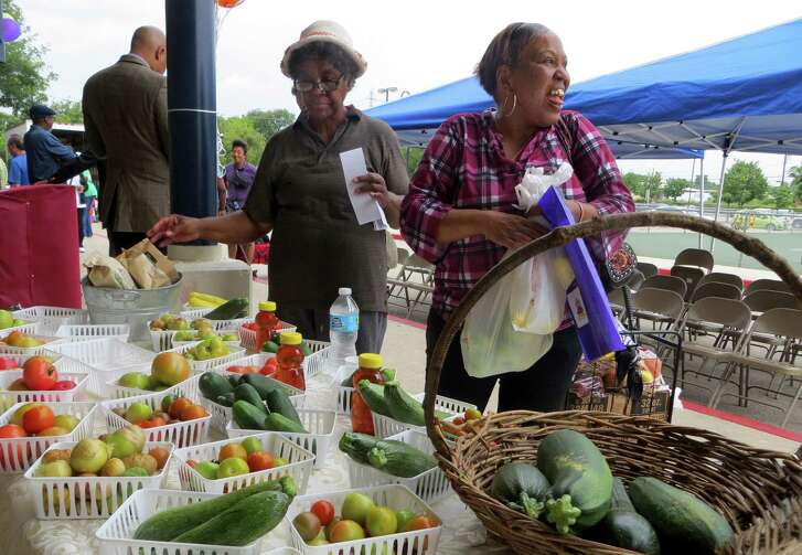 Betty Pryor (left) and Vernice Terrell shop at the farmers market at Wheatley Middle School held from 10 a.m. to 1 p.m. on the first Saturday of the month on the city's East Side.