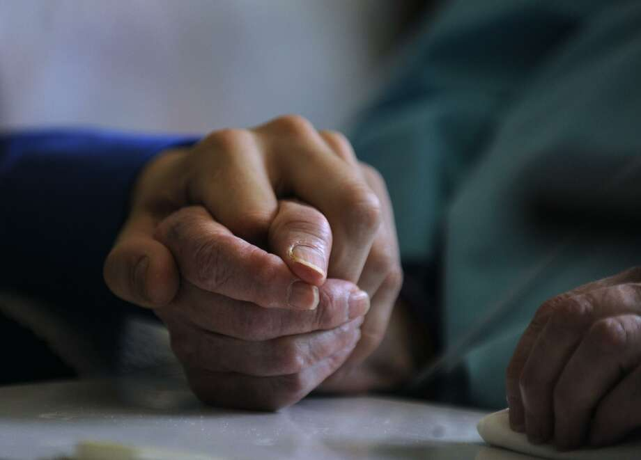A social worker takes the hand of a palliative care patient. Photo: Kathryn Scott Osler / Kathryn Scott Osler / Denver Post Via Getty Images / This content is subject to copyright.