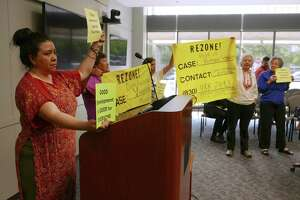People concerned about lower-income residents being pushed out of their neighborhoods by gentrification hold signs and chant after a meeting of the Mayor's Task Force on Preserving Dynamic and Diverse Neighborhoods on April 14, 2015. The committee was formed after the displacement of hundreds of residents from the Mission Trails mobile home, which was rezoned for apartments.