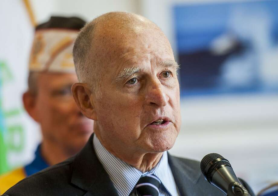 Gov. Jerry Brown, center, answers questions from the media at the Great Park Gallery about the proposed veterans cemetery in Irvine, Calif., Friday, May 12, 2017.  Photo: Paul Rodriguez, Associated Press