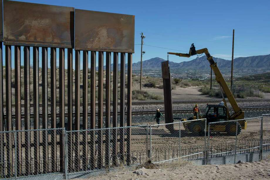 Workers lift a segment of a new fence into place on the border with Mexico in Sunland Park, N.M. Photo: Rodrigo Abd, STF / Stratford Booster Club