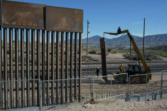 Workers lift a segment of a new fence into place on the border with Mexico in Sunland Park, N.M.