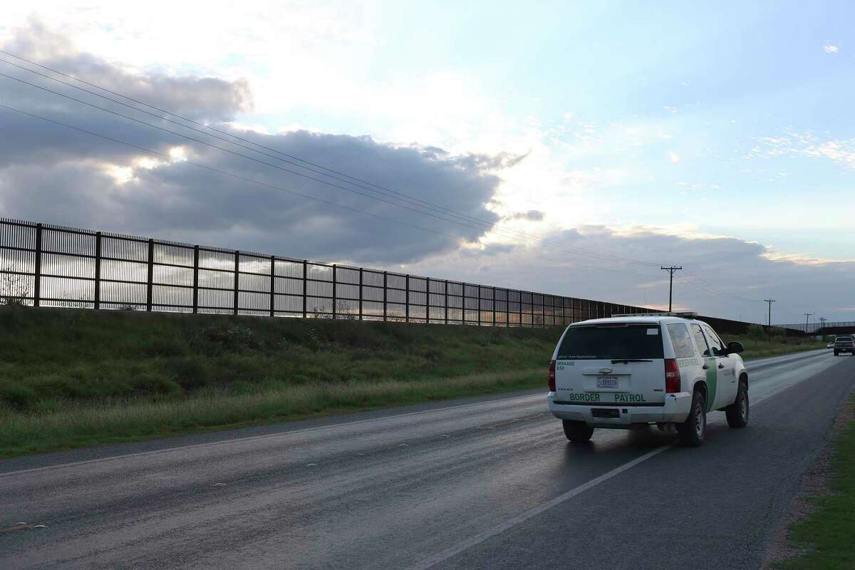 A U.S. Border Patrol unit makes its way along U.S. 281 by the U.S.-Mexico border fence near San Benito. The wall stretches in a series of broken links from Brownsville to Hidalgo County.