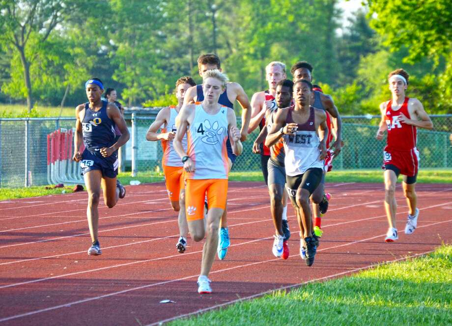 Edwardsville's Jack Pifer, front, leads a pack of runners after the first 400 meters of the 1,600-meter run during the Southwestern Conference Meet at EHS.